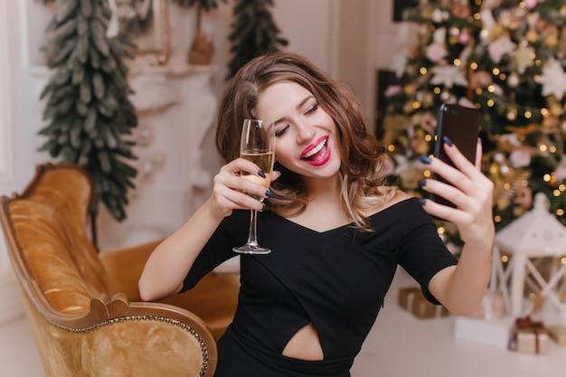 Femme romantique en tenue noire élégante, levant un verre de vin et faisant selfie. dame émotionnelle s'amusant pendant les vacances d'hiver et se photographiant.