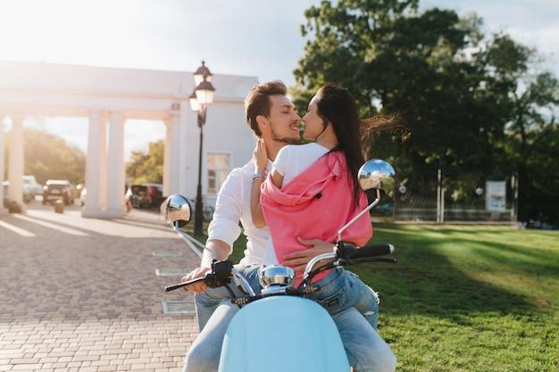 Femme romantique en vêtements roses touchant doucement son petit ami avec amour, assis sur un scooter
