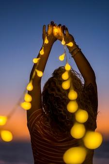 Femme romantique vue de dos avec beaucoup de lumières jaunes