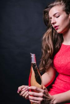 Femme en rose assise avec une bouteille ouverte