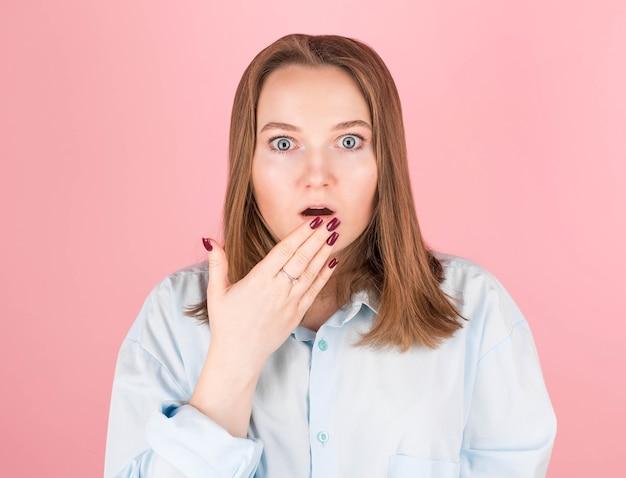 Femme sur rose en chemise bleue faisant le geste oops