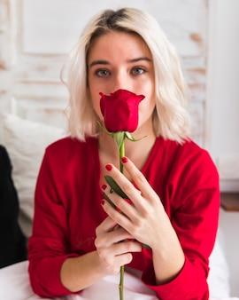 Femme avec une rose rouge le jour de la saint-valentin