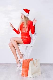 Femme en rouge assis sur une chaise avec téléphone