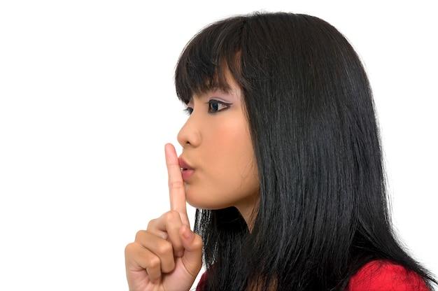 Femme en rouge dit silencieux avec sa main isolée sur fond blanc