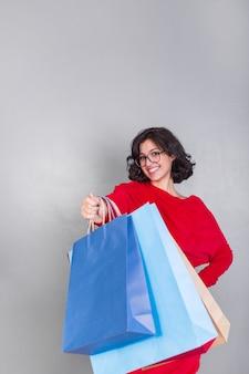 Femme en rouge donnant des sacs