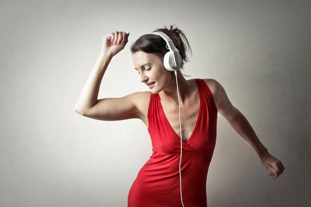Femme en rouge écoutant de la musique