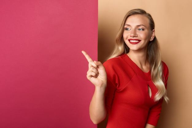 Femme en rouge pointant sur panneau d'affichage vide