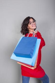 Femme en rouge avec des sacs à provisions dans le dos