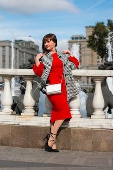 Une femme en rouge se tient devant la balustrade du pont de la ville. en manteau et chapeau.