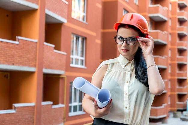 Femme avec rouleaux de plans sur chantier