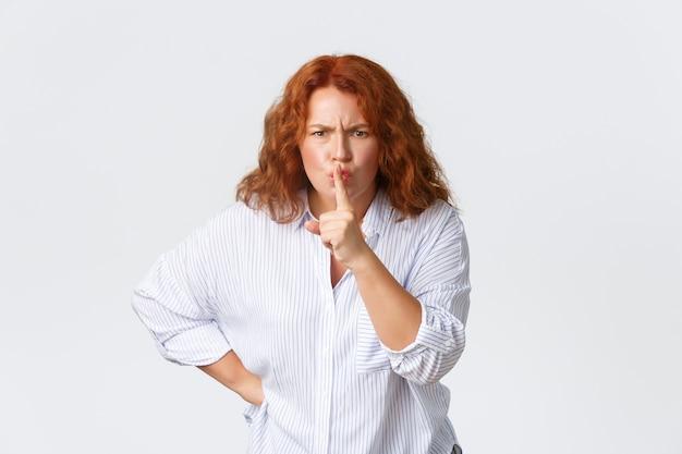 Femme rousse d'âge moyen en colère et dérangée, taisant et fronçant les sourcils, appuyez du doigt sur les lèvres pour dire tais-toi, en disant être calme, déçue par un mauvais comportement, gronder enfant, mur blanc.
