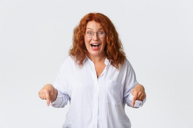 Une femme rousse d'âge moyen impressionnée et étonnée réagit aux nouvelles impressionnantes, pointant du doigt vers le bas, haletant, retenant son souffle d'excitation, mur blanc.