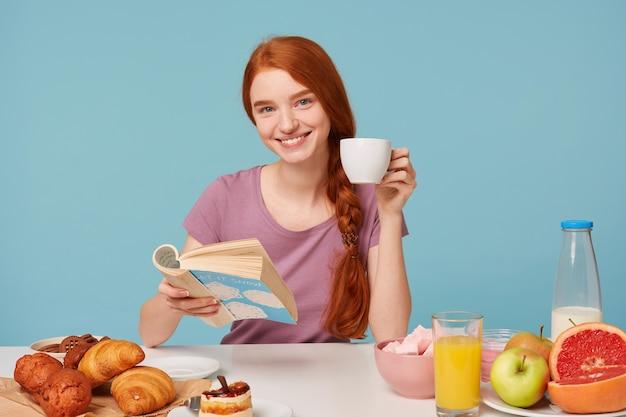 Femme rousse agréablement souriante aux cheveux tressés, assis à une table, tient une tasse blanche avec une boisson délicieuse