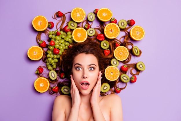 Femme rousse artistique posant avec des fruits dans ses cheveux