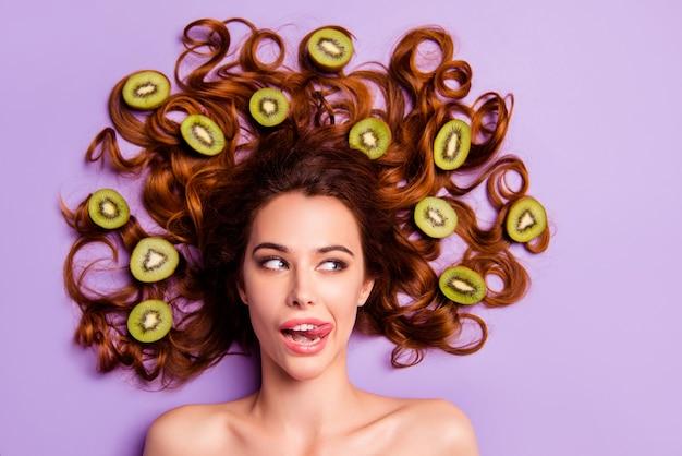 Femme rousse artistique posant avec kiwi dans ses cheveux