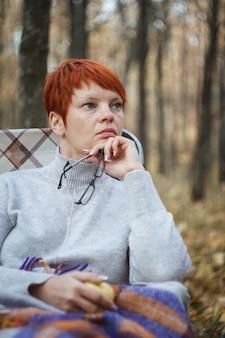 Femme rousse assise dans une chaise longue pliante sur un fond de forêt en automne