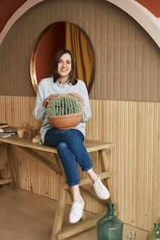 Femme rousse assise à la table tient un grand cactus rond dans ses mains qui fait pousser des plantes d'intérieur