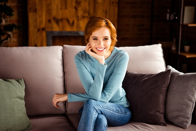 Femme rousse aux cheveux courts posant à l'intérieur sur le canapé