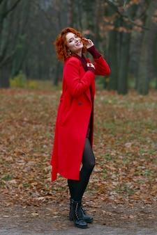 Femme rousse aux cheveux en manteau rouge sur fond d'automne.