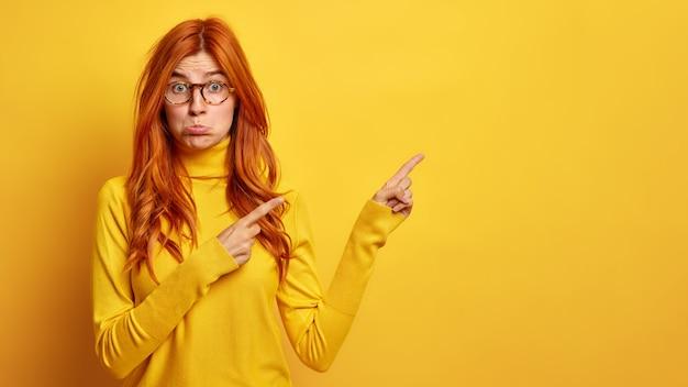 Une femme rousse aux taches de rousseur insatisfaite porte un sac à main sur la lèvre inférieure et montre un espace vide montre quelque chose de mauvais porte des lunettes à col roulé décontractées.