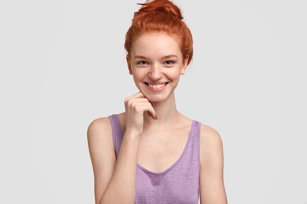 Une femme rousse aux taches de rousseur positive a un sourire charmant, croit que le rire augmente la durée de vie