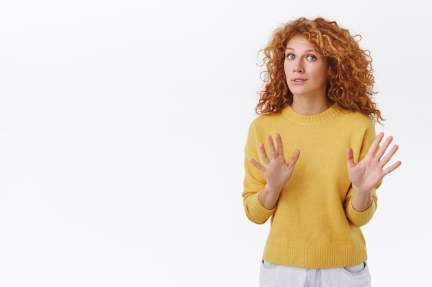 Une femme rousse bouclée inquiète et inquiète calme la personne, en disant de ne pas tirer, en levant les bras, en suppliant d'arrêter, en ayant l'air effrayée ou nerveuse, en persuadant quelqu'un de lâcher le pistolet, mur blanc
