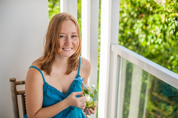Femme rousse buvant un mojito sur la terrasse