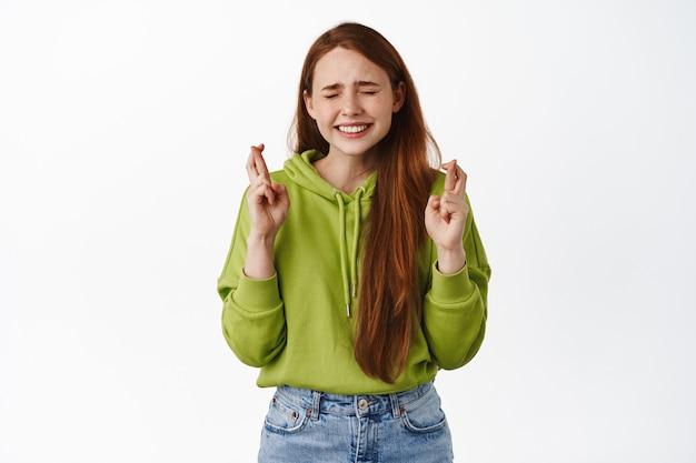 Une femme rousse chanceuse croise les doigts pour la bonne chance, ferme les yeux et souhaite, souriante pleine d'espoir, attendant que le rêve se réalise, anticipant les résultats de l'examen sur blanc