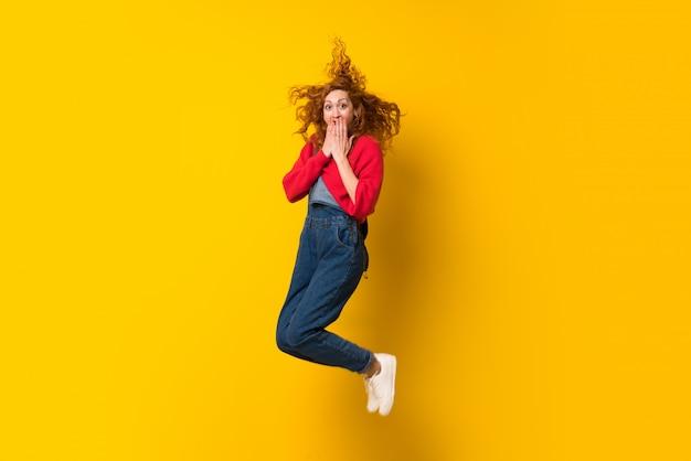 Femme rousse avec une combinaison sautant par-dessus un mur jaune isolé