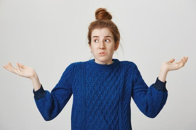 Femme rousse confuse haussant les épaules et regardant ailleurs perplexe