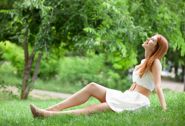 Femme rousse couchée sur l'herbe verte