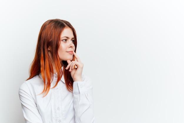 Femme rousse dans une chemise blanche