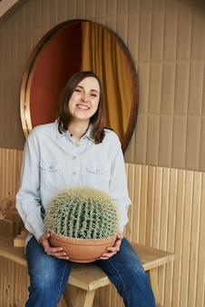 Une femme rousse dans un jean chemise bleue tient un grand cactus rond et rit
