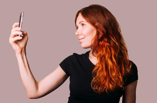 Femme rousse dans un t-shirt noir prend un selfie sur son smartphone