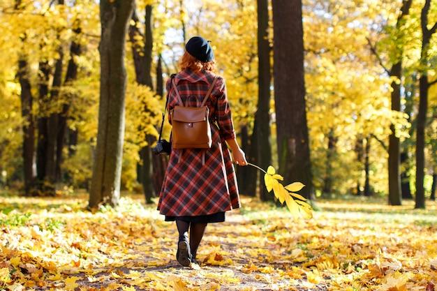 Une femme rousse élégante en manteau à carreaux béret noir et sac à dos se promène dans le parc en tenant du jaune sec...