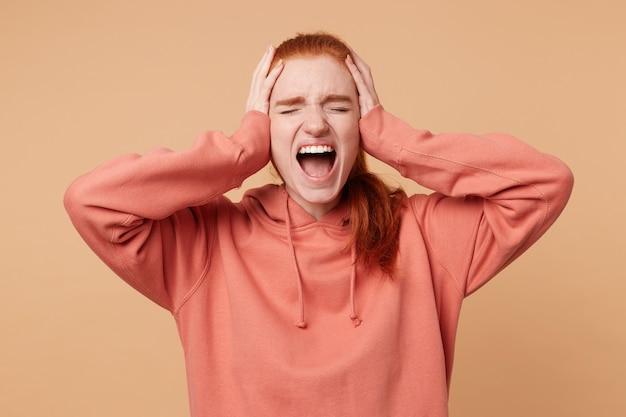 Femme rousse émotionnelle avec queue de cheval ouvrant largement sa bouche, hurlant fort
