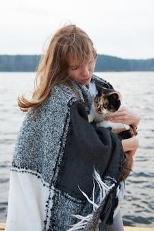 Femme rousse, enveloppée dans une couverture à carreaux, tenant un chat, debout sur la jetée près du lac. automne nuageux neat weat