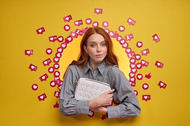 Une femme rousse examine un nouveau sac, le montre au public abonné, tenant un sac à main dans les mains