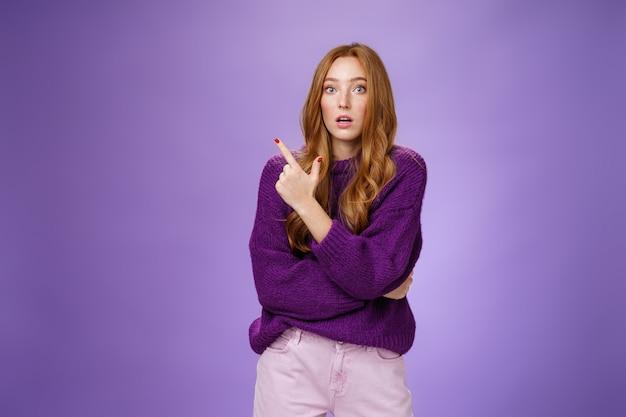 Une femme rousse excitée et étonnée ouvre la bouche et lève les sourcils, interrogée en voyant une chose choquante pointant vers le coin supérieur gauche, posant une question impressionnée et surprise par-dessus le mur violet.
