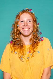 Femme rousse faire la fête avec des confettis dans ses cheveux