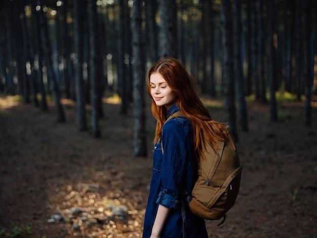 Femme rousse gaie avec un sac à dos dans le voyage de bois