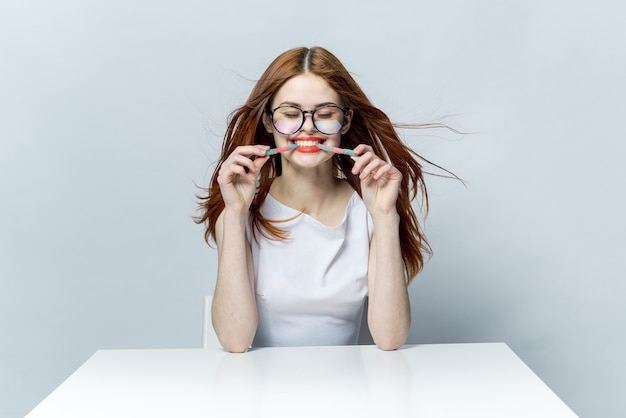 Femme rousse glamour assis à la table et manger de la marmelade avec des lunettes