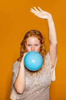 Femme rousse gonflant un ballon bleu