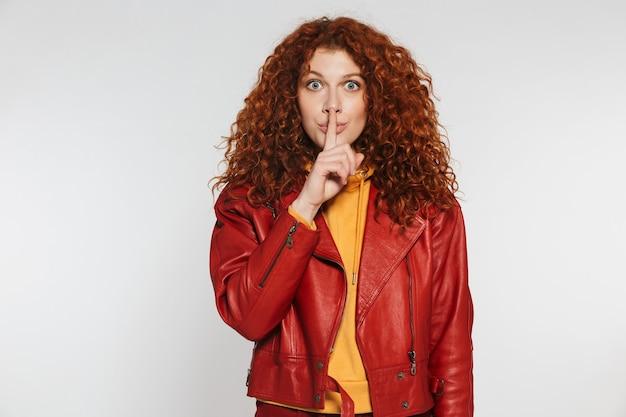 Femme rousse heureuse de 20 ans portant une veste en cuir souriante et tenant le doigt sur ses lèvres isolées sur un mur blanc