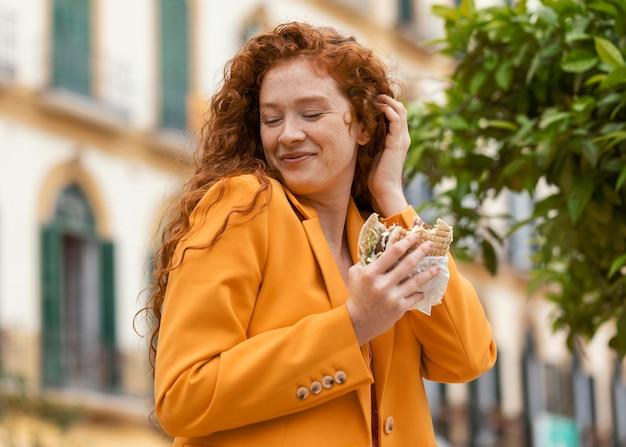 Femme rousse heureuse, manger de la nourriture de rue