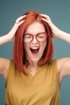 Femme rousse heureuse et positivité à lunettes criant tenant la tête par les mains.