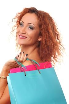 Femme rousse heureuse avec des sacs à provisions