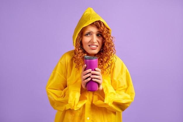 Femme rousse en imperméable jaune et tasse thermique isolée sur violet