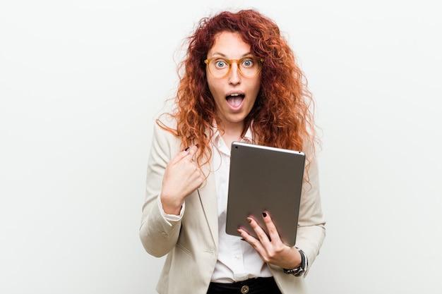 Femme rousse jeune caucasien tenant une tablette surprise pointant sur lui-même, souriant largement.