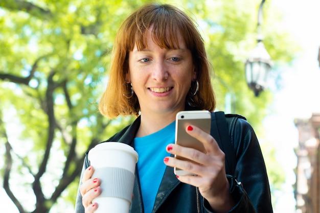 Femme rousse jeune tape le message avec le téléphone mobile.